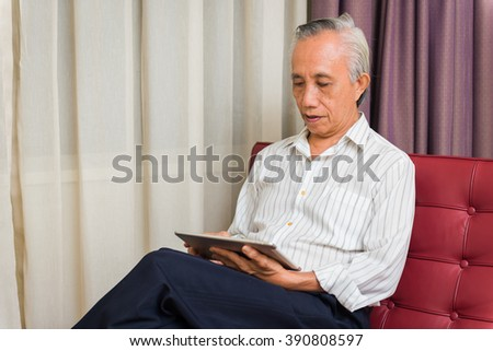 Asian businessman at sofa working using tablet.