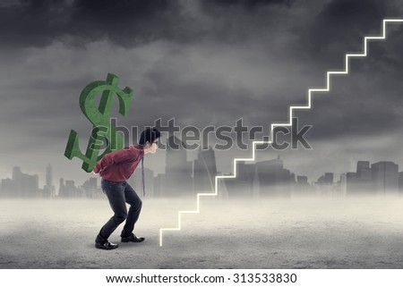 Asian businessman carrying a dollar sign walking up a staircase