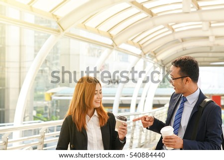 Asian businessman cheerful and feeling relax talking with business woman partner