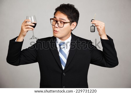 Asian businessman choose drink or drive on gray background
