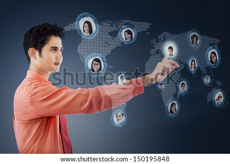 Asian businessman clicking on social networking map over blue digital world map - stock photo