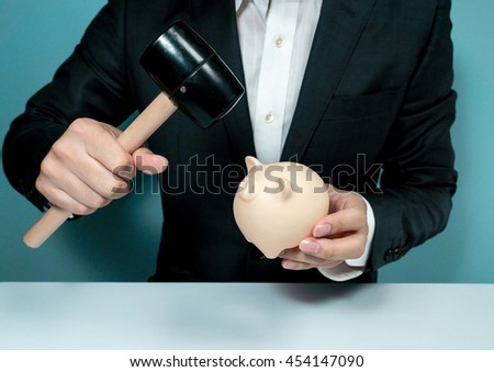 Asian businessman crushing piggy bank - stock photo