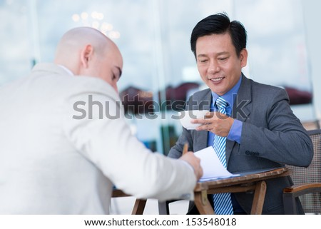 Asian businessman drinking coffee while his partner signing an important document on the foreground  - stock photo