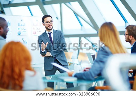 Asian businessman explaining his point of view to colleagues - stock photo