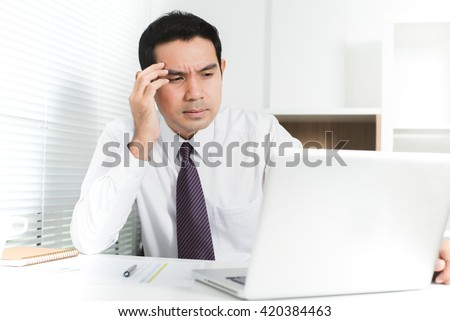 Asian businessman getting stressed (upset) at work, putting his hand on temple
