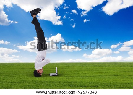 Asian businessman headstand outdoor with blue sky - stock photo
