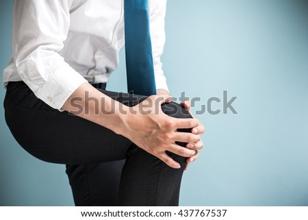 Asian businessman holding knee