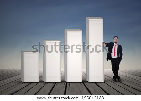 Asian businessman in black suit standing next to bar chart with blue sky background - stock photo