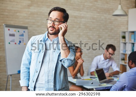 Asian businessman in eyeglasses speaking on cellphone in working environment - stock photo