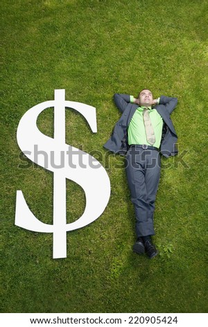 Asian businessman in grass next to dollar sign - stock photo