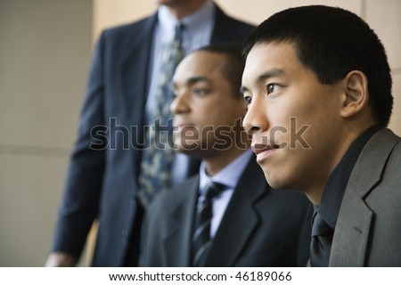 Asian businessman in the foreground with African-American businessman and a third businessman in the background. Horizontal format. - stock photo