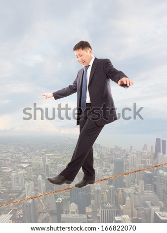 Asian businessman keeping his balance on a rope over a big city