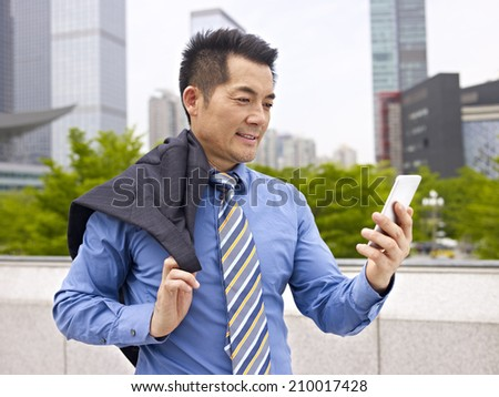 asian businessman looking at cellphone. - stock photo