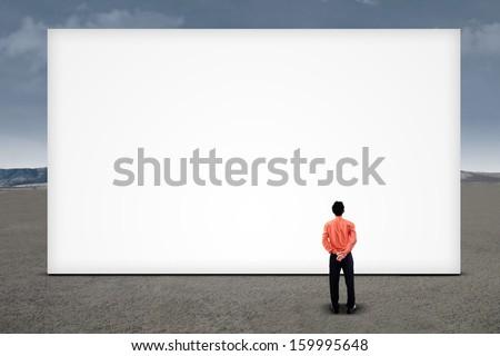 Asian businessman looking at empty billboard under cloudy sky - stock photo