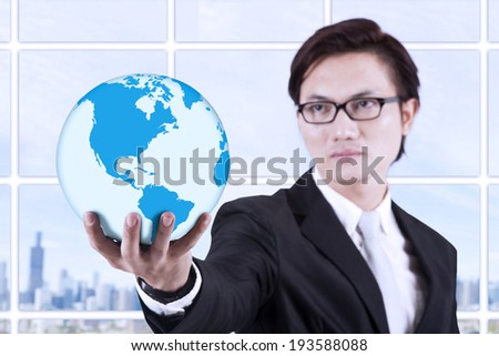 Asian businessman looking smart with glasses holding a globe - stock photo