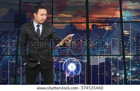 Asian Businessman looking the tablet on theTrading graph over the cityscape at night and world map background,Business financial concept - stock photo