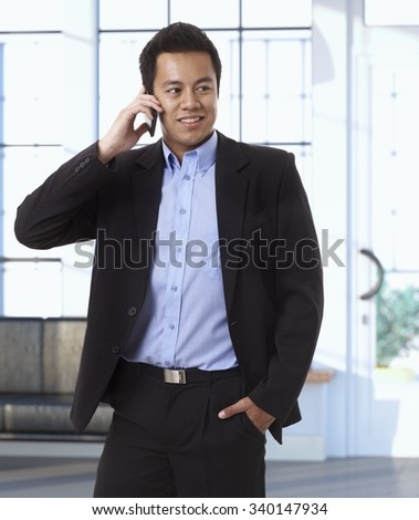 Asian businessman on the phone at office, looking away. - stock photo