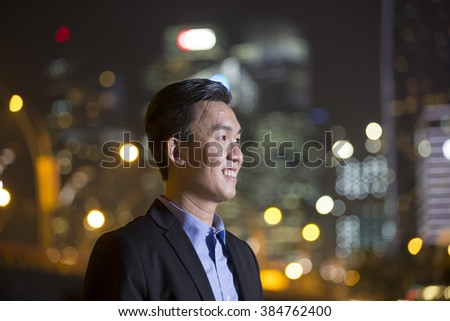 Asian businessman outdoors using his Smart phone at night in modern city. Working late and Business on the go concept. - stock photo