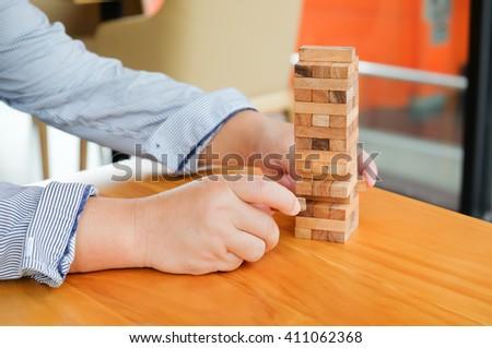asian businessman playing wood blocks stack game - stock photo