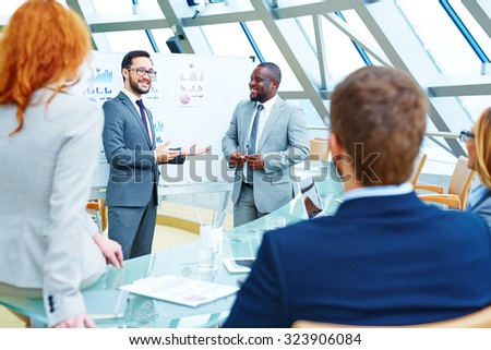 Asian businessman presenting colleagues their new business partner - stock photo