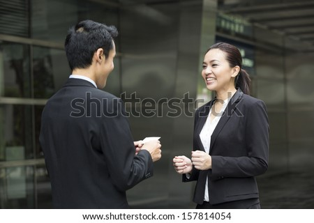 Asian Businessman presenting his business card to a businesswoman