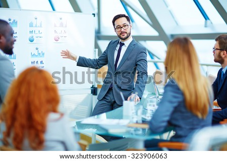 Asian businessman presenting review of financial data to colleagues