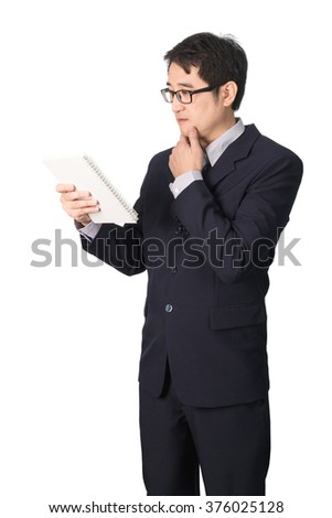 Asian businessman reading notebook or diary for checking, isolated on white background.