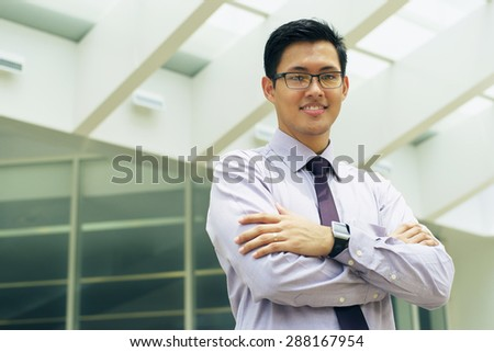 Asian businessman relaxing outside office building. The man does yoga on a bridge and smiles with eyes closed in prayer position - stock photo