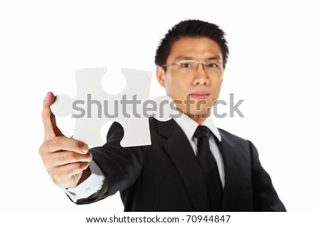 Asian businessman showing a piece of jigzaw puzzle, over white background