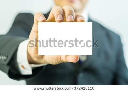 Asian businessman showing business card ,Man's hand showing business card ,closeup shot - can be used for display type your text message,vintage color,selective focus. - stock photo