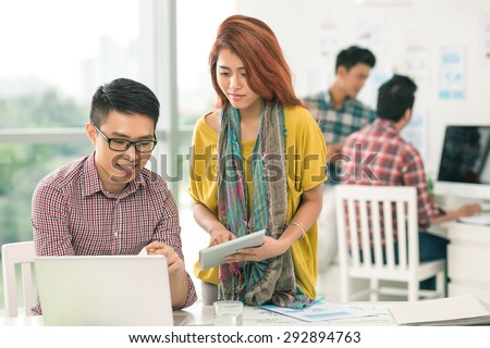 Asian businessman showing something on the laptop screen to his female colleague