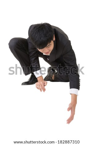 Asian businessman sit and bend down to help somebody, full length portrait isolated on white. - stock photo