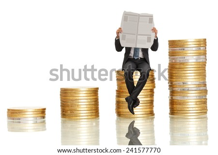 asian businessman sitting and reading newspaper on coin stack,investment concept on white background - stock photo