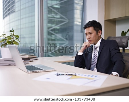 asian businessman sitting in office, looking depressed. - stock photo