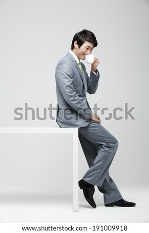 Asian businessman sitting on desk with coffee