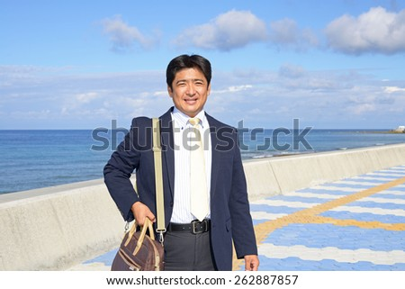 Asian businessman standing by the sea