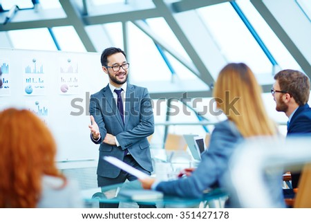 Asian businessman standing by whiteboard during presentation - stock photo
