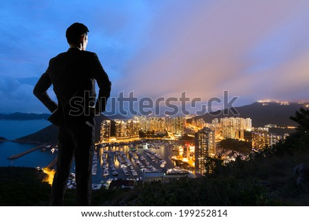Asian businessman standing in the hill and looking at the skyscrapers and harbor in Aberdeen, Hong Kong, Asia. - stock photo