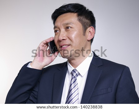 asian businessman talking on phone. - stock photo