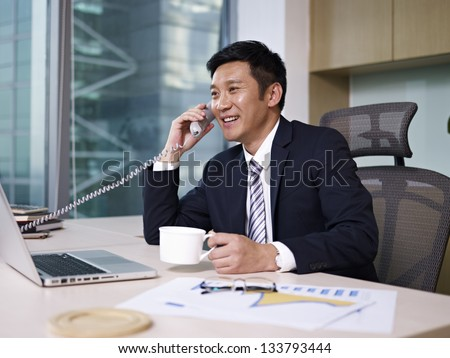 asian businessman talking on phone in office.