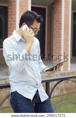 Asian businessman talking on the phone and holding tablet in hand.