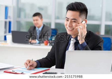 Asian businessman talking on the phone and writing while his colleague working in background - stock photo