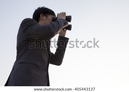 Asian businessman using binoculars during sunset being isolated from the sky - business vision / business opportunities / market watch concept