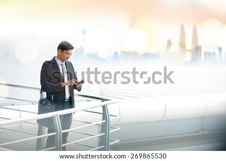 Asian businessman using smartphone, standing at modern office building, skyline at background. - stock photo