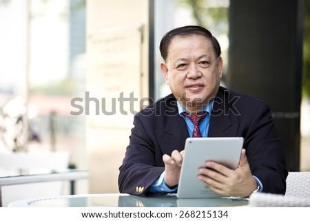 Asian businessman using tablet - stock photo