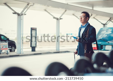 Asian businessman waiting for taxi at the airport - stock photo