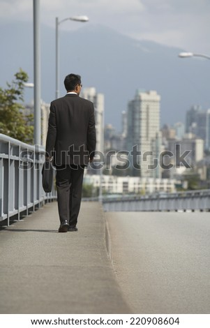 Asian businessman walking on urban bridge