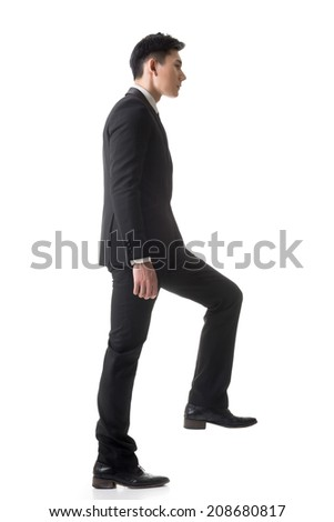 Asian businessman walking up on stairs, full length portrait isolated on white background.