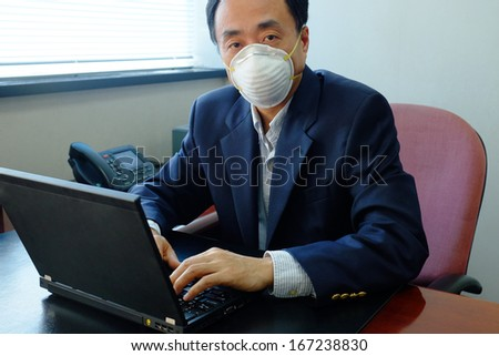 Asian businessman wearing protective mask in an office with air pollution - stock photo