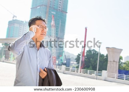 Asian businessman with construction site background - stock photo